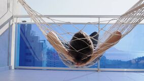 Child laying and relaxing in hammock hanging on balcony of apartment. Back view. Kid swinging and dreaming, thinking