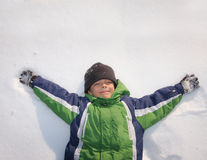 Child laying on snow Royalty Free Stock Images