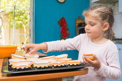 The child lays on baking tins Easter cupcakes Stock Photos