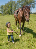 Child leading a horse. A young girl leading a horse in a field. Start 'em young Royalty Free Stock Images