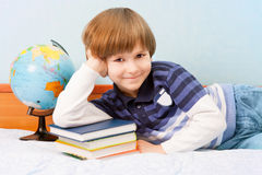 Child leans on bed with books and globe Stock Images