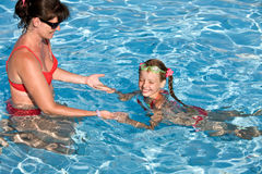 Child learn swim in swimming pool. Stock Photos
