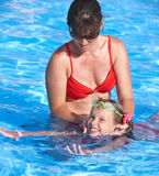 Child learn to swim in swimming pool with teacher. Royalty Free Stock Image