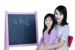 Child learning alphabet with her mother Royalty Free Stock Photos