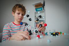Child learning chemistry, making model of a molecule, engineering and STEM