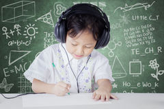 Child learning in class while wearing headphones Royalty Free Stock Photos
