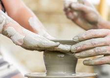 Child learning how to make a pot, old potter h Stock Image