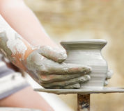 Child learning how to make a pot, old potter h Stock Photo