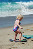 Child learning how to skimboard in Laguna Beach, CA Royalty Free Stock Photos
