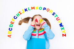 Child learning letters of alphabet and reading Stock Photography