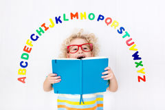 Child learning letters of alphabet and reading. Happy preschool child learning to read and write playing with colorful roman alphabet letters. Educational abc Stock Photo