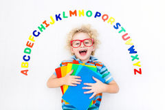 Child learning letters of alphabet and reading. Happy preschool child learning to read and write playing with colorful roman alphabet letters. Educational abc Stock Image