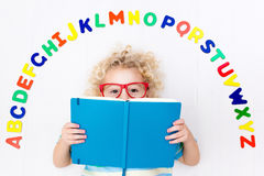 Child learning letters of alphabet and reading. Happy preschool child learning to read and write playing with colorful roman alphabet letters. Educational abc Royalty Free Stock Photo