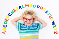 Child learning letters of alphabet and reading. Happy preschool child learning to read and write playing with colorful roman alphabet letters. Educational abc Stock Photos