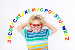 Child learning letters of alphabet and reading. Happy preschool child learning to read and write playing with colorful roman alphabet letters. Educational abc Stock Photography