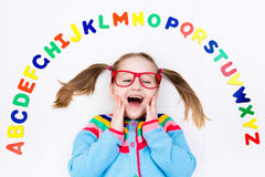 Child learning letters of alphabet and reading Royalty Free Stock Photography