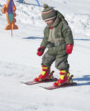 Child learning skiing. Small child learning to ski on a slope with children slalom in a skiing school Stock Photos