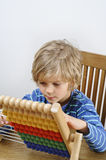 Child learning to count on an abacus royalty free stock images