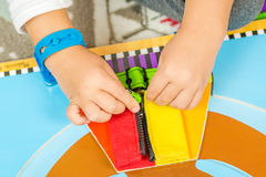 Child is learning to do up zip stock photo