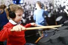 Child learning to play drums stock photo