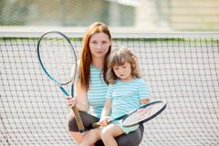 Child learning to play tennis with her mother on outdoor court. Little girl with tennis racket. Active exercise for kids and family royalty free stock image
