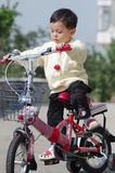 Child learning to ride. A baby learns to ride a new bicycle Stock Photos