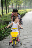 Child Learning to Ride. A child learns how to ride her bicycle, with the help of Mom Stock Photos