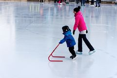 A child learning to skate on an outdoor rink in Montreal royalty free stock photo