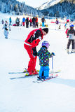 The child learning to ski and man on the slope in Bansko, Bulgaria Stock Image