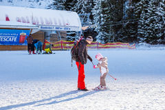 The child learning to ski and man on the slope Stock Image