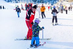 The child learning to ski and man on the slope Royalty Free Stock Photo
