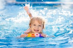 Child learning to swim. Kids in swimming pool