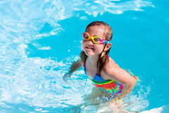 Child learning to swim in pool Royalty Free Stock Photography
