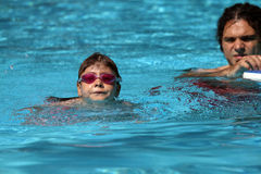 Child learning to swim, swimming lesson. Child learning to swim, taking swimming lesson Royalty Free Stock Images