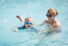 Child Learning to swim. A women helps a happy young boy learn how to swim in a swimming pool Royalty Free Stock Images