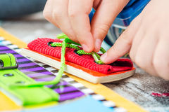 Child is learning to tie the laces royalty free stock photo