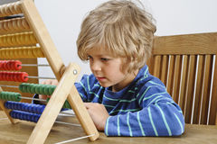 Child learning to use an abacus royalty free stock photography
