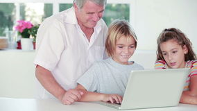 Child learning to use laptop with grandfather stock video