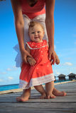Child learning to walk on tropical vacation Royalty Free Stock Image