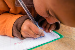Child learning to write arabic. Little kid writing arabic word in primary public school. Photo taken in Morocco Royalty Free Stock Photos