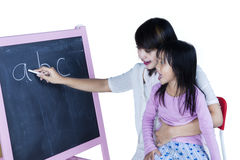 Child learns alphabet with her mom. Cute little girl learns alphabet while her mother writing the letter with a chalk on blackboard stock photos