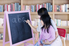Child learns alphabet in library. Picture of little girl learns alphabet with her teacher writing the letter on chalkboard, shot in the library stock image