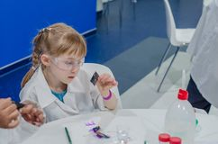 Children conduct experiments with colors. A child learns chromatography in kid`s scientific lab Royalty Free Stock Photography