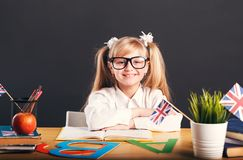 Child Learns English. Happy smiling girl learning English language, working table with books, letters and flag royalty free stock images