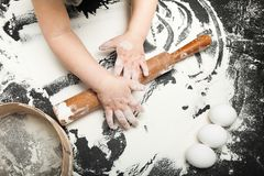 Child learns to cook on a black table, with flour in the kitchen royalty free stock image