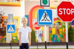 A child learns to cross the road at a pedestrian crossing, traffic rules for children