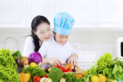 Child learns to cut vegetables in kitchen Royalty Free Stock Images