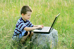 Child learns to laptop Royalty Free Stock Image