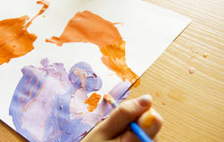 The child learns to paint. Child draws on a white sheet with colored paints, the child learns to paint stock photography