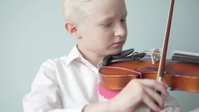 A child learns to play the violin in a music school.  stock footage
